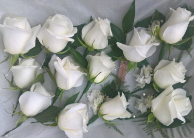 Bella Poppy Flower Design, Chichester - Flowers, Florist,Weddings, Funerals, Dried Flowers, Bouquets - White Rose Button Holes laid out on white silk