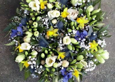 Bella Poppy Flower Design-Chichester-Flowers-Florist-Weddings-Funerals-Bouquets- A funeral arrangement of mix of purple, yellow and white flowers with green leaves