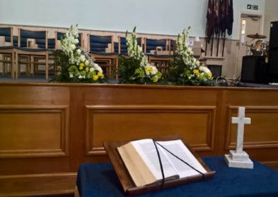 Three funeral arrangments of white and yellow flowers in a church