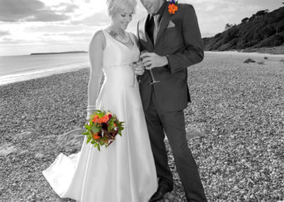 Bride and Groom on a beach with orange bouquet - wedding flowers