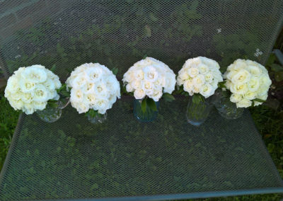 5 white rose bouquets in jars on a bench - wedding flowers