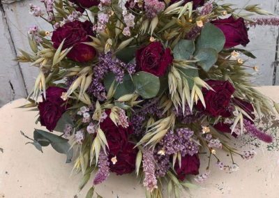 Bouquet of dark red roses and outs - dried flowers