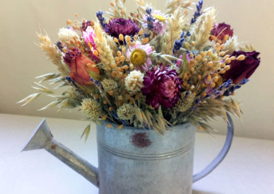 watering can containing dried flower arrangment