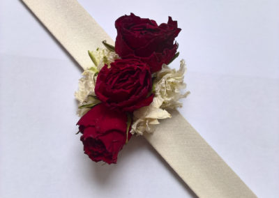 Corsage of red and white dried flowers