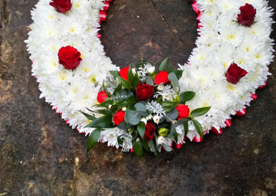 Funeral tribute of red and white flowers in a horse shoe shape - wedding flowers