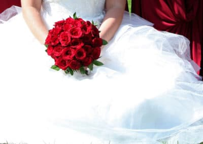 Bride holding red rose bouquet - wedding flowers